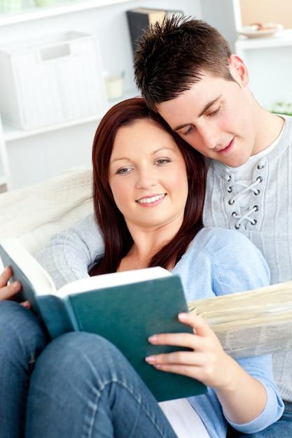 Heureux couple lisant un livre dans le salon allongé sur le canapé Photo Premium