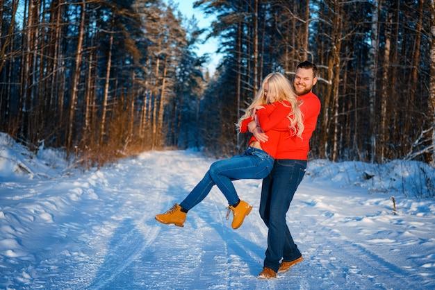 Heureux couple marchant dans la forêt enneigée Photo Premium