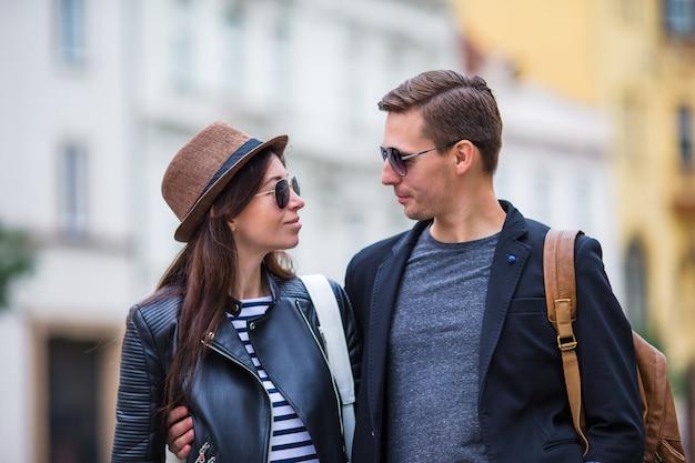 Heureux couple marchant en europe. sourire amants profiter de paysage urbain avec des monuments célèbres. Photo Premium