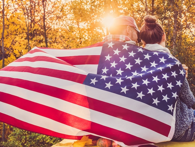 Heureux couple marié tenant le drapeau américain Photo Premium