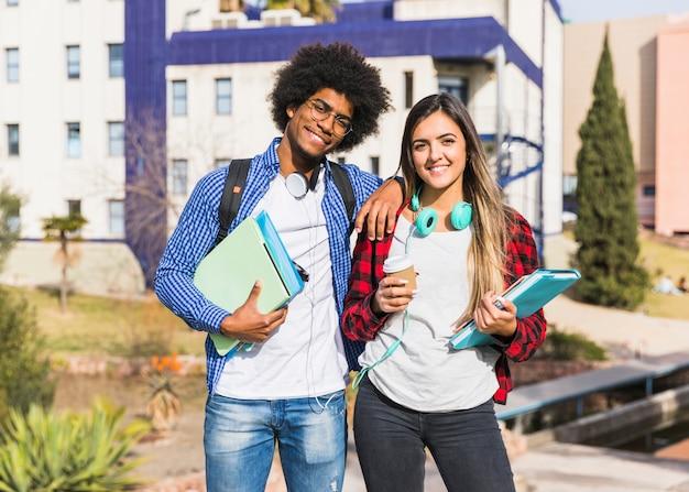 Heureux couple métisse posant devant le bâtiment de l'université Photo gratuit