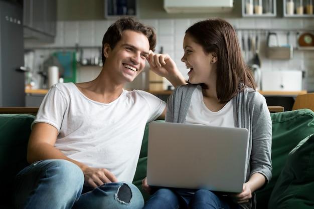 Heureux couple millénaire rire à l'aide d'un ordinateur portable ensemble sur le canapé de la cuisine Photo gratuit