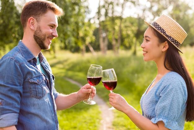 Heureux couple multiethnique tinter des verres à vin dans le parc Photo gratuit