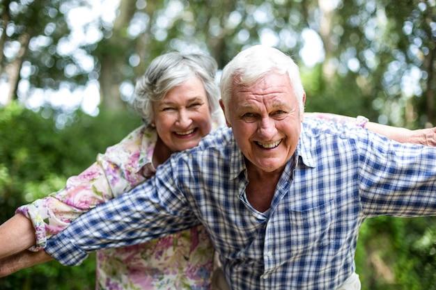 Heureux couple de personnes âgées avec les bras tendus dans la cour arrière Photo Premium