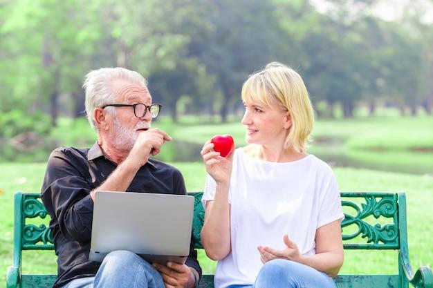 Heureux couple de personnes âgées dans le parc tenant coeur dans le concept de la saint-valentin amour Photo Premium