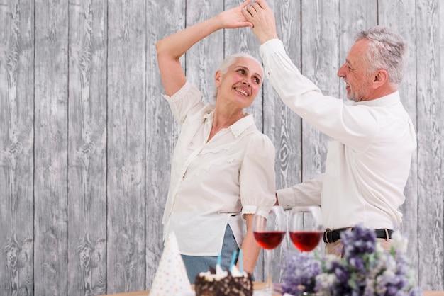 Heureux couple de personnes âgées dansant à la fête d'anniversaire Photo gratuit