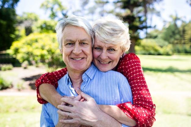 Heureux couple de personnes âgées embrassant dans le parc Photo Premium