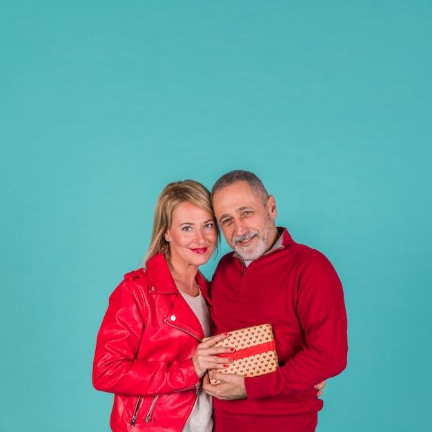 Heureux couple de personnes âgées posant avec des cadeaux Photo gratuit