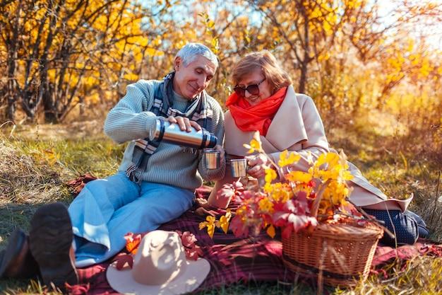 Heureux couple de personnes âgées prenant le thé dans la forêt d'automne et pique-nique Photo Premium