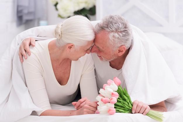 Heureux Couple De Personnes âgées Romantique Sur Le Lit, Tenant Dans La Main Des Fleurs De Tulipes Photo gratuit