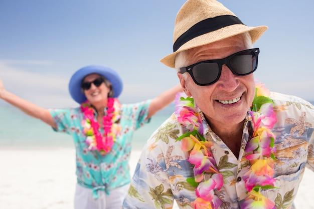 Heureux couple de personnes âgées s'amuser ensemble sur la plage Photo Premium