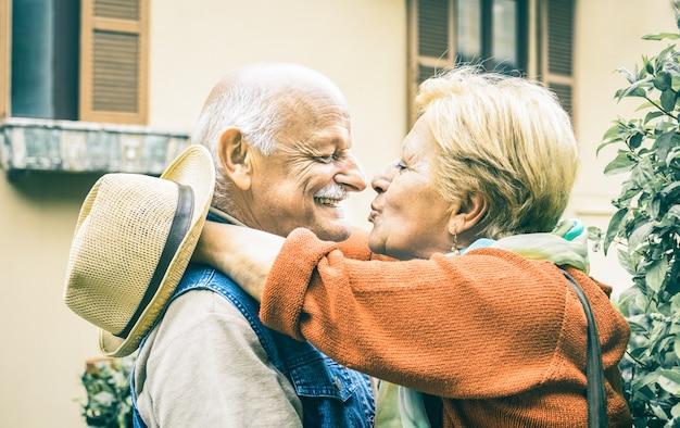Heureux couple de personnes âgées s'amuser à s'embrasser en plein air en vacances Photo Premium