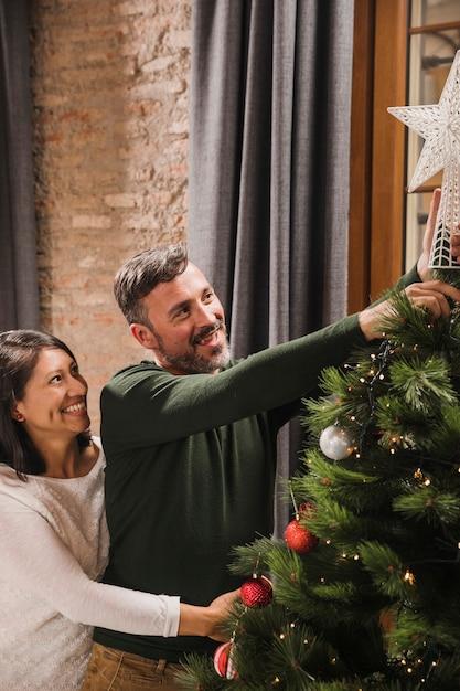 Heureux Couple De Personnes âgées Souriant Près De L'arbre De Noël Photo gratuit