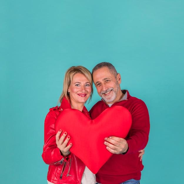 Heureux couple de personnes âgées tenant grand coeur rouge Photo gratuit