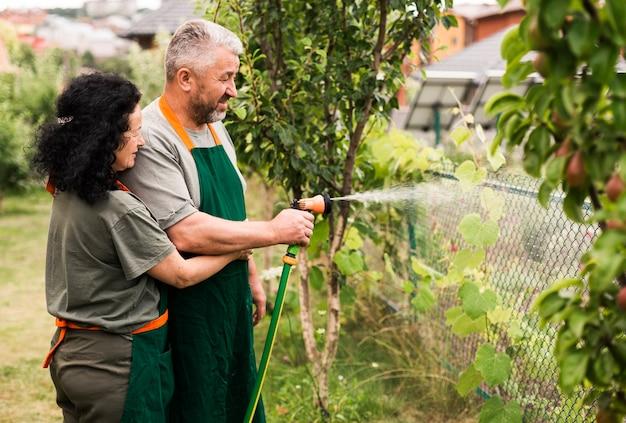 Heureux couple de personnes âgées avec un tuyau d'arrosage Photo gratuit