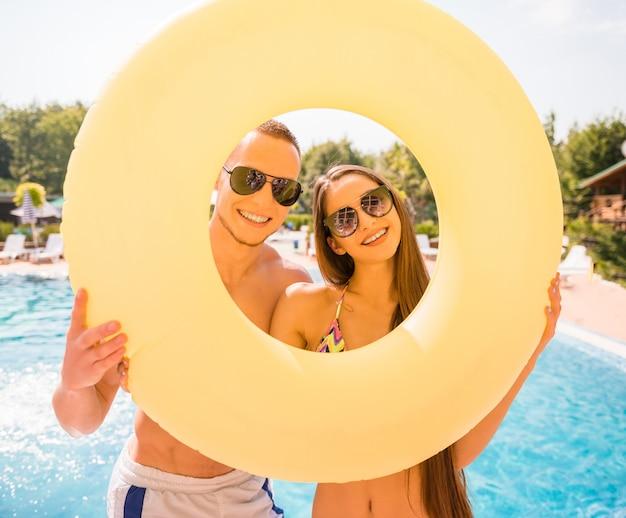 Heureux couple pose avec anneau en caoutchouc dans la piscine. Photo Premium