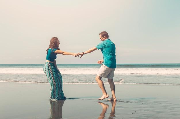 Heureux couple romantique s'amuser sur la plage Photo gratuit