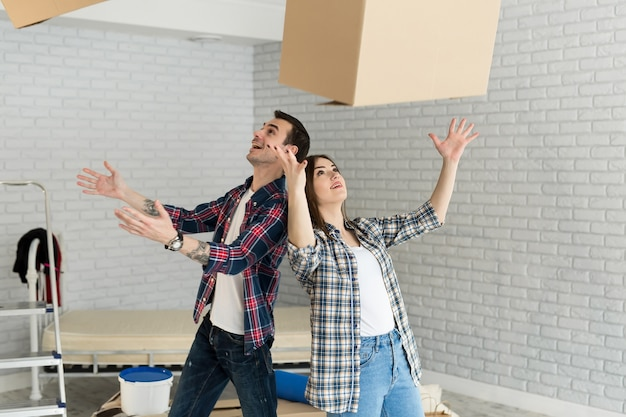 Heureux Couple S'amuse Avec Des Boîtes En Carton Dans Une Nouvelle Maison Au Jour Du Déménagement Photo Premium