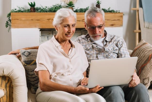 Heureux couple senior assis sur un canapé à la recherche d'un ordinateur portable Photo gratuit