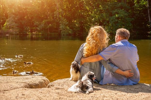 Heureux Couple Senior Assis Sur Le Lac Au Soleil Avec Leurs Chiens. Concept De Vacances En Famille Dans La Nature Photo Premium
