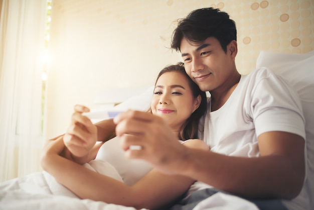 Heureux Couple Souriant Après Avoir Découvert Un Test De Grossesse Positif Dans La Chambre Photo gratuit