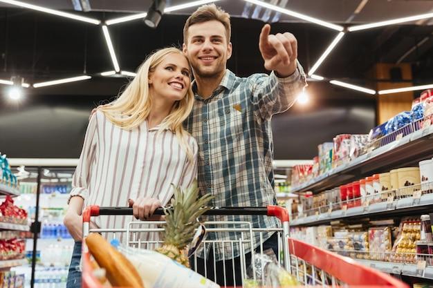 Heureux Couple Souriant Avec Un Chariot Shopping Photo gratuit