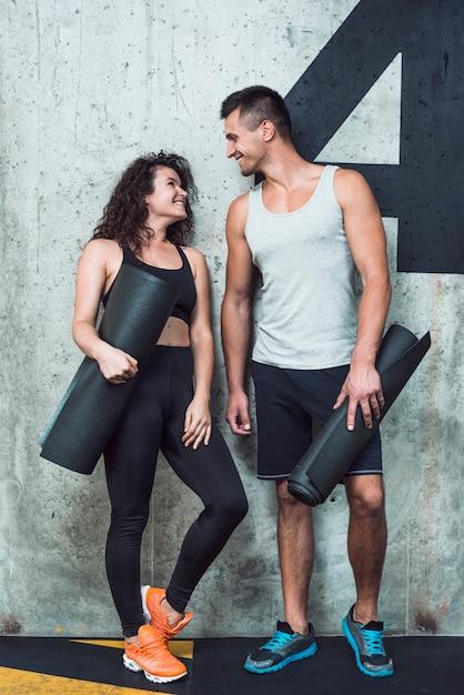 Heureux couple sportif avec tapis d'exercice se regardant Photo gratuit