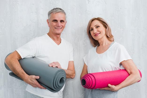 Heureux couple tenant penchée mur blanc tenant roulé tapis de yoga Photo gratuit
