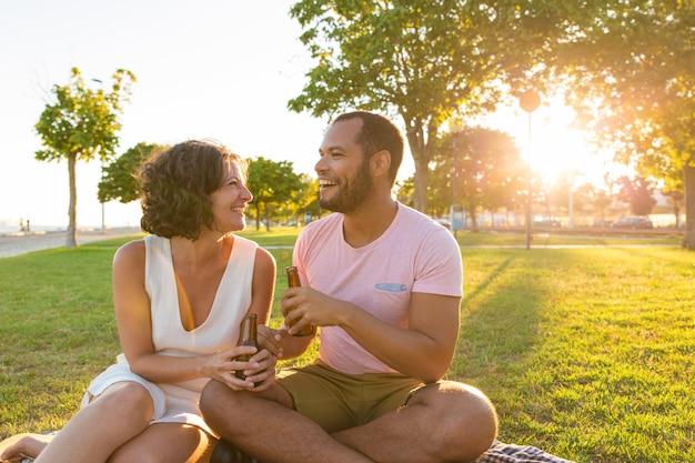 Heureux couple en train de bavarder autour d'une bouteille de bière Photo gratuit