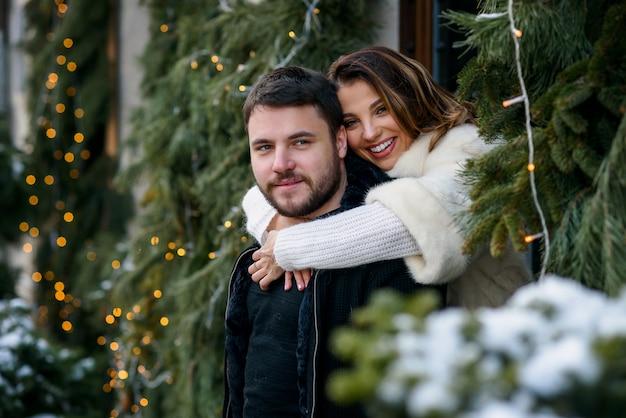 Heureux couple en vêtements chauds s'embrassant sur l'arbre de noël avec des lumières. vacances d'hiver, noël et nouvel an. Photo Premium