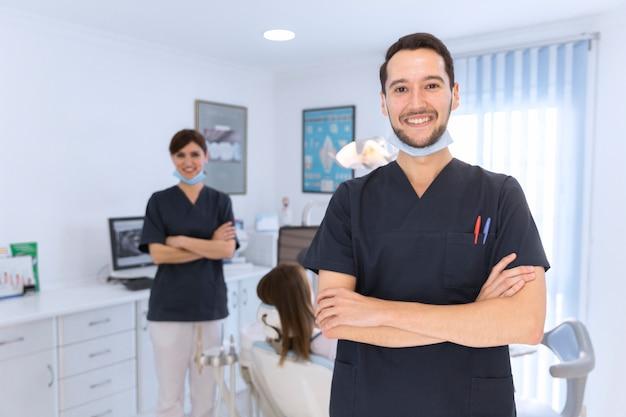 Heureux dentiste homme et femme en clinique dentaire Photo gratuit