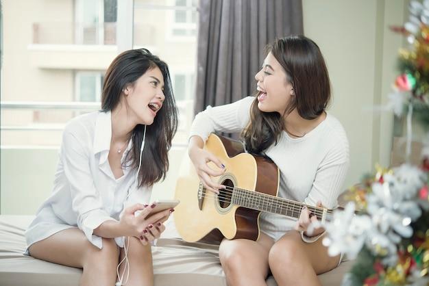 Heureux Deux Amis Jouant De La Guitare Et Chantant Sur Le Lit. Photo Premium