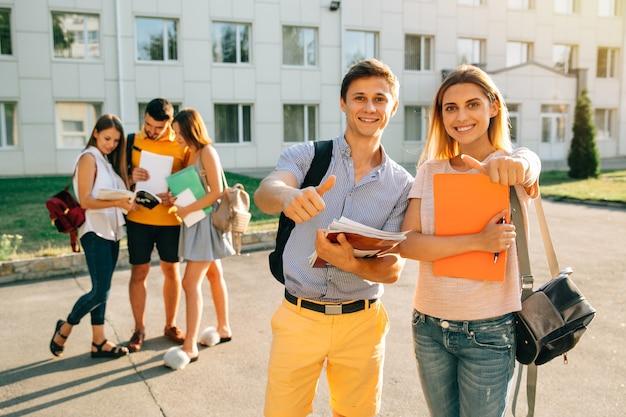 Heureux deux jeunes étudiants avec des cahiers et des sacs à dos en souriant et en montrant le pouce vers le haut Photo gratuit