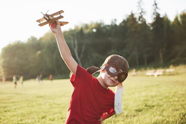Heureux Enfant En Casque Pilote Jouant Avec Un Avion Jouet En Bois Et Rêvant De Devenir Volant Photo Premium