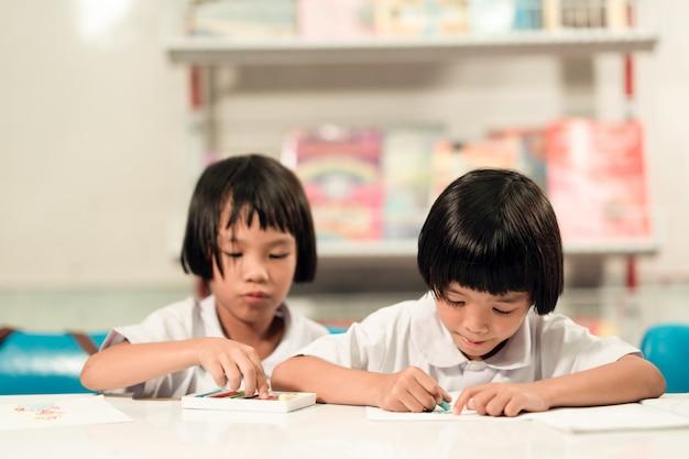 Heureux enfant étudiant jouant et apprenant en classe. Photo Premium