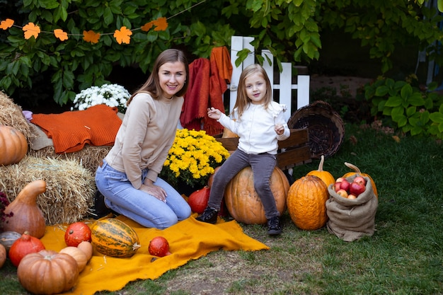 Heureux enfant et mère avec citrouille à l'extérieur à l'halloween Photo Premium