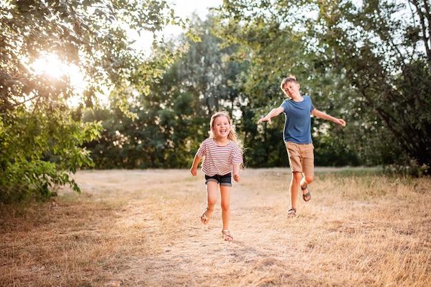 Heureux Enfants Garçon Et Fille Gambader Dans Le Parc. Le Frère Aîné Joue Avec Sa Sœur Dans La Nature Dans Les Rayons Du Soleil Couchant D'une Journée D'été. Photo Premium