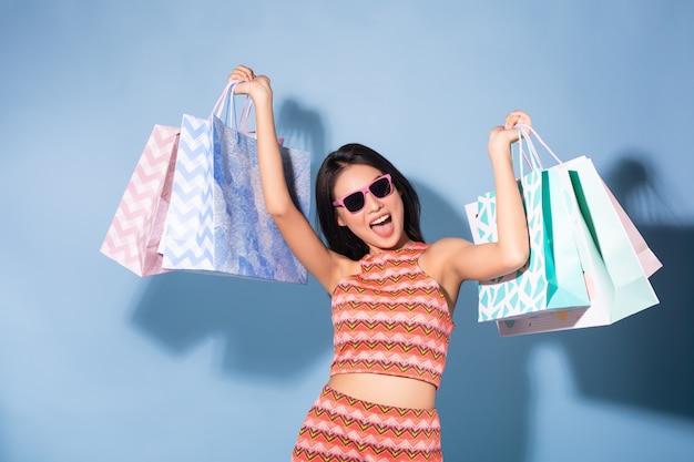 Heureux été asiatique jolie fille tenant des sacs à provisions et lunettes de soleil à la recherche de suite Photo Premium