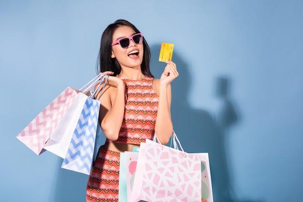 Heureux été jolie fille asiatique tenant des sacs à provisions tout en cartes de crédit et lunettes de soleil à la recherche de suite Photo Premium