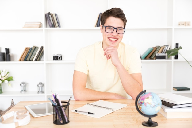 Heureux étudiant assis avec un cahier vide Photo gratuit
