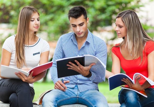 Heureux étudiants étudiant En Plein Air Assis Sur Un Banc Photo Premium
