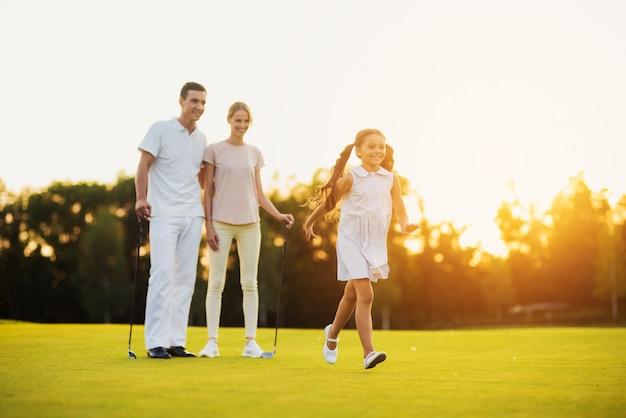Heureux famille loisirs golfeurs marcher par fairway. Photo Premium