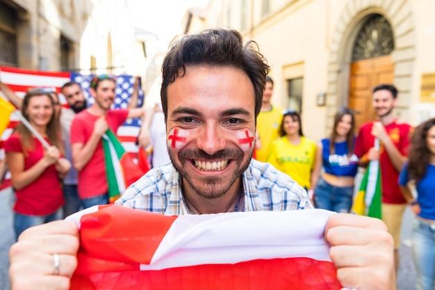Heureux fan avec le supporter du drapeau anglais lors d'un match international Photo Premium