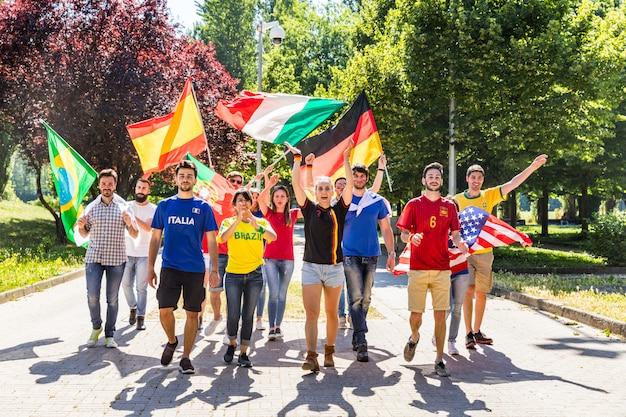 Heureux fans fans de différents pays marchant et chantant ensemble Photo Premium