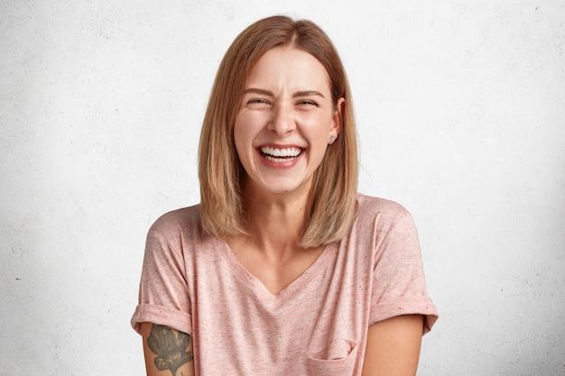 Heureux à La Femme Agréable Avec Un Large Sourire Sincère Rit Joyeusement à La Caméra, écoute Des Anecdotes, Isolé Sur Blanc Photo gratuit