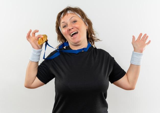 Heureux Femme Sportive D'âge Moyen En T-shirt Noir Avec Bandeau Et Médaille D'or Autour De Son Cou Le Montrant Souriant Joyeusement Debout Sur Un Mur Blanc Photo gratuit