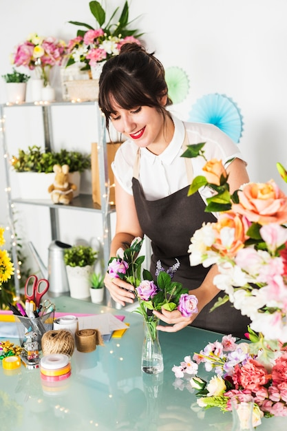 Heureux fleuriste femelle triant des fleurs dans un vase Photo gratuit
