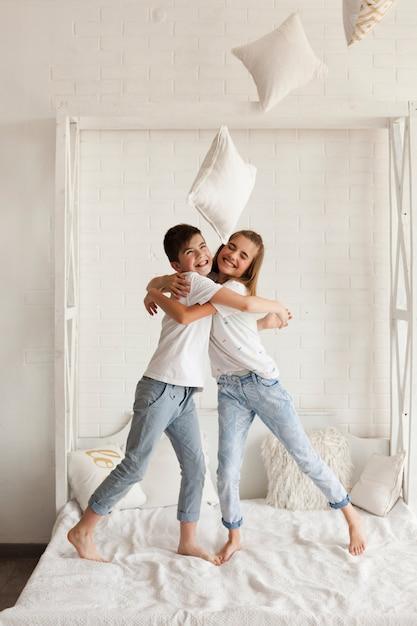 Heureux frère et soeur embrassant sur le lit à la maison Photo gratuit