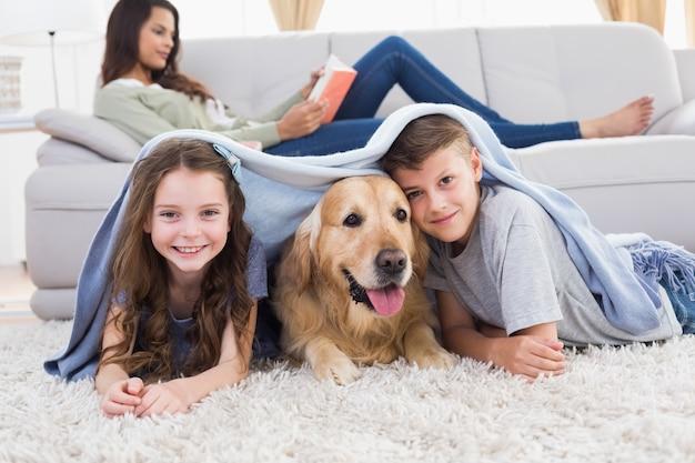 Heureux frères et sœurs avec chien sous couverture Photo Premium