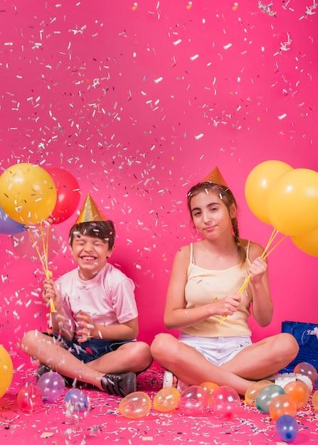 Heureux frères et sœurs, profitant de la fête avec des ballons et des confettis sur fond rose Photo gratuit
